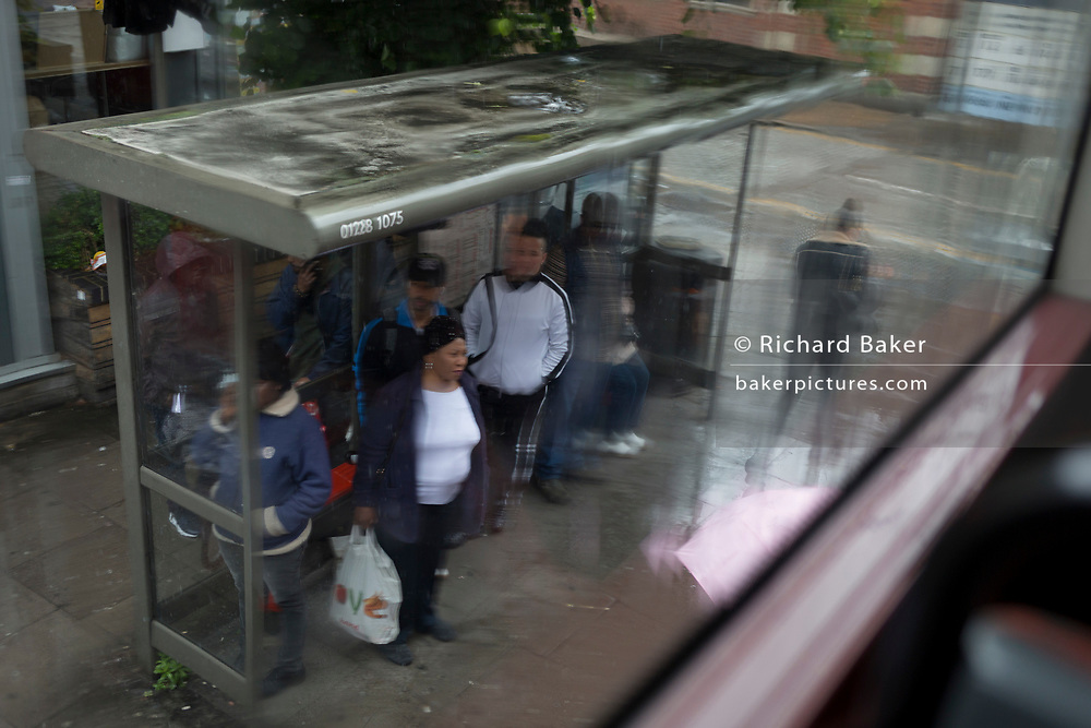 Passengers shelter under the roof of a bus stop before their next bus on the Walworth Road, in south London, on 15th June 2019, in London, England.