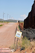 The international border between Naco, Arizona, USA and Naco, Sonora, Mexico is indicated by a metal wall.  A sign prohibits trespassing on to private property that borders the wall in Arizona.