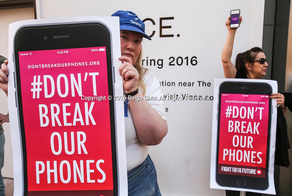 2月23日,示威者在洛杉矶一家苹果专卖店外示威。当天,示威活动在美国、甚至美国以外超过30多个城市的多家苹果零售店展开,声援苹果公司拒绝帮助美国执法部门解除一部在去年12月2日美国加州南部圣贝纳迪诺恐怖袭击案中枪手的智能手机开机密码。新华社发 (赵汉荣摄)<br /> Demonstrators with a banner protest outside the Apple store, Tuesday, Feb. 23, 2016, in Los Angeles, the United States. Protesters assembled in more than 30 cities around the world to lash out at the FBI for obtaining a court order that requires Apple to make it easier to unlock an encrypted iPhone used by a gunman in December's mass murders in California. (Xinhua/Zhao Hanrong)(Photo by Ringo Chiu/PHOTOFORMULA.com)<br /> <br /> Usage Notes: This content is intended for editorial use only. For other uses, additional clearances may be required.