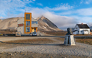 New-Aalesund, the northernmost permanent settelment in the World and a research town at western Spitsbergen, Svalbard, Norway. In the foreground the statue of Roald Amundsen. Photo from August 2019.