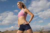 Female jogger with hands on hips, outdoors