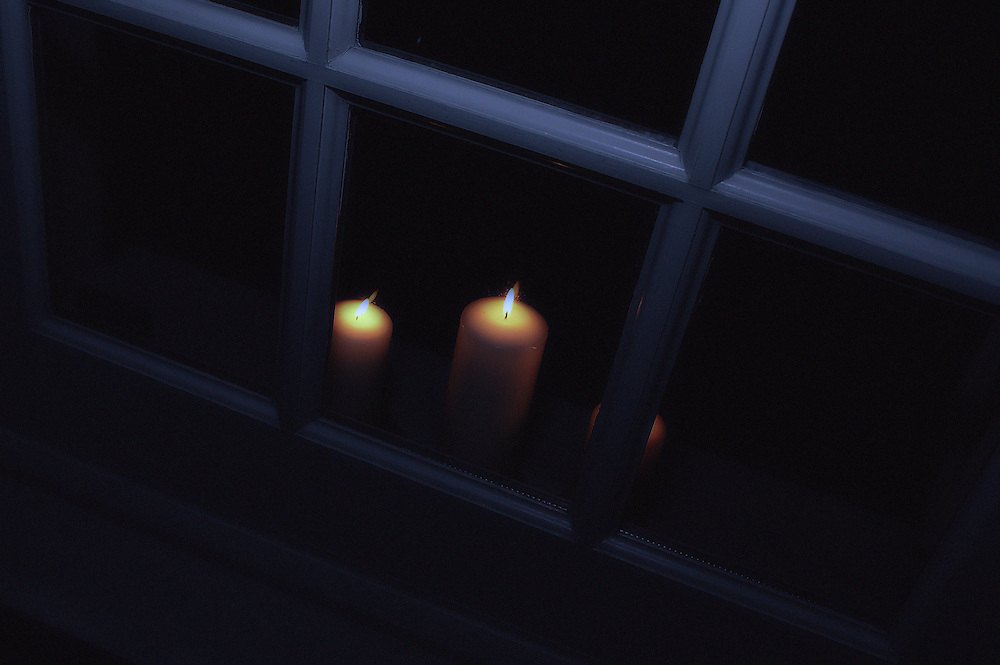 Candles viewed a window frame at night.