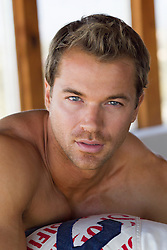 All American man with blue eyes, brown hair and no shirt at home