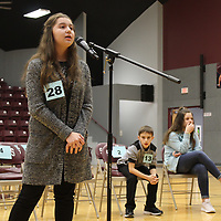 Hatley seventh-grader Sierra Lochala, left, takes a turn at spelling a word in the championship round of the Monroe County Spelling Bee. The other finalists competing against her were Hatley fifth-grader Owen Wilson and Amory seventh-grader Anna Claire Tutor.