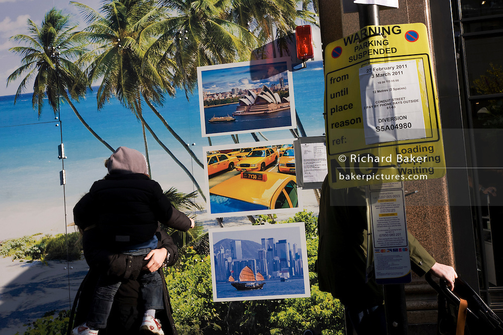 Mother carrying child past street construction site showing tropical beach paradise and images of world cities with a No Parking sign.
