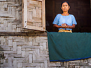 11 NOVEMBER 2014 - SITTWE, MYANMAR: A Rakhine Buddhist woman stands in the window of her thatched home in a Rakhine IDP camp near Sittwe. About 700 Rakhine Buddhist families live in an Internal Displaced Persons (IDP) camp on the edge of Sittwe. The people in the camp lost their homes in Sittwe in 2012 when Buddhist mobs rioted and burnt down Rohingya Muslim homes and businesses. The Buddhists' homes were mistakenly destroyed by other Buddhists or intentionally destroyed by retaliating Muslims during the 2012 violence. Unlike the Muslims, who live in much larger camps further from Sittwe, the Buddhists are allowed to come and go into downtown Sittwe and their homes are built in the traditional style, on stilts with large windows, and so are much more comfortable.   PHOTO BY JACK KURTZ