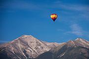 A hot air balloon soars high above the Rocky Mountains in Colorado