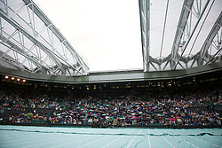 LONDON, ENGLAND - Monday, June 20, 2011: Spectators shelter from the rain, and the roof closes on Centre Court, during the Ladies' Singles 1st Round match on day one of the Wimbledon Lawn Tennis Championships at the All England Lawn Tennis and Croquet Club. (Pic by David Rawcliffe/Propaganda)