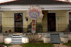 10 December, 05.  New Orleans, Louisiana.  Post Katrina aftermath.<br /> A lavish Mardi Gras Indian feathered head dress decorates the front of a devastated home in Gentilly, New Orleans east where the flood 'coffee stain' demonstrates just how high the water came.<br /> Photo; &copy;Charlie Varley/varleypix.com