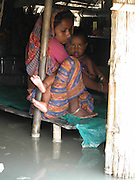 jamela khatun, an woman carries with her baby on a platform where her house room under water  at chalakurar village, about 325 kilometers (203 miles) southwest of Gauhati, capital of northeastern Indian state of Assam, thursday, July 10, 2003. Floods and mudslides in the northeastern states of Assam has killed at least 28 people over the past week and uprooted more than 500,000 from their homes, while 25 lakhs render homeless. (AP Photo/Shib Shankar Chatterjee)