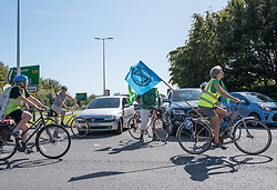 © Licensed to London News Pictures. 14/09/2019. Felton, North Somerset, UK. Cyclists circle the roundabout outside the entrance to Bristol Airport for an Extinction Rebellion protest against the proposed expansion plans for Bristol Airport. The campaigners say that there will be more air pollution from increased flights which are not counted in the airport's target to be carbon neutral by 2025, that there will be a loss of greenbelt land, more noise pollution from more flying, traffic congestion, and ill health from respiratory and cardiac disease. Campaigners say a recent report found that the incidence of asthma and respiratory diseases was on average 17% higher among those living within 6.2 miles of a major airport and that cardiac diseases were 9% more common. Photo credit: Simon Chapman/LNP.
