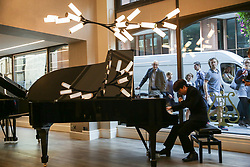 London, UK. 18 September, 2019. A Steinway artist plays a Steinway piano at Steinway Hall beneath a limited edition Steinway Haara chandelier. Only ten chandeliers were produced as a collaboration celebrating craftsmanship between world renowned piano makers Steinway & Sons UK and bespoke sculptural lighting company Cameron Design House. Inspired by Steinway's iconic black lacquer gloss finish, it comes complete with beautiful brass accents and the iconic Steinway & Sons emblem.