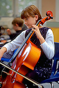 Young girl playing her cello in school.