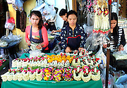 A young girl looks up from the tedious job of stringing small flowers into ornate items at Bangkok's Flower Market.