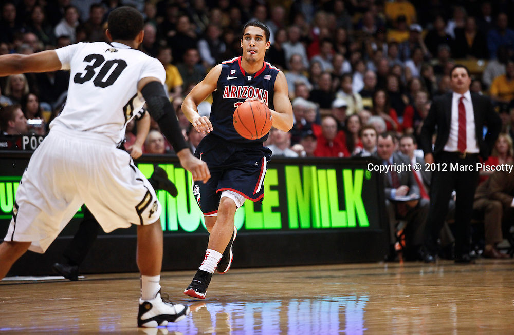 SHOT 1/21/12 5:37:41 PM -  Arizona's Nick Johnson #13 pushes the ball upcourt as Colorado's Carlon Brown #30 closes in during their PAC 12 regular season men's basketball game at the Coors Events Center in Boulder, Co. Colorado won the game 64-63..(Photo by Marc Piscotty / © 2012)