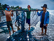 29 JULY 2017 - AIRKUNING, BALI, INDONESIA: Fishermen roll up the net after hauling it in in Airkuning, a Muslim fishing village on the southwest corner of Bali. Villagers said their regular catch of fish has been diminishing for several years, and that are some mornings that they come back to shore with having caught any fish.    PHOTO BY JACK KURTZ
