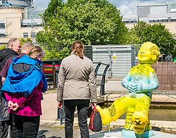 Pictured: Oor Wullie Bucket Art Trail. Leith, Edinburgh, Scotland, United Kingdom, 17 June 2019. An art trail of 200 Oor Wullie sculptures have appeared in Scottish cities overnight in a mass arts event that lasts until August 30th. The sculptures will be auctioned to raise money for Scotland's children's hospital charities. There are 5 in the Leith area, and 60 in Edinburgh altogether. Sailoor Wullie by The Leith Agency at Commercial Quay near the Scottish Government building, Victoria Quay with bemused tourists.<br /> Sally Anderson | EdinburghElitemedia.co.uk