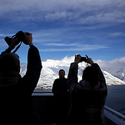 Tourists photograph the snow capped mountains around Queenstown from the Skyline Gondola after the biggest snow storm in New Zealand in the past 50 years. Queenstown, New Zealand, 16th August 2011. Photo Tim Clayton