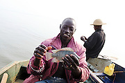 Augustino Ssekisaka holds up a Nile perch just caught in Lake Victoria by his friend and frequent fishing companion, Siggando Francis. Here in Ggaba, a small town in southern Uganda that almost entirely subsists on the fishing industry, the locals have contributed to the dangerous overfishing of the lake despite strict regulations from Tanzania, Uganda, and Kenya. Fishermen continue to keep fish that are far below the required minimum weight and employ dymanite and poison.