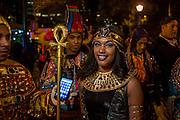 New York, NY - 31 October 2015. A woman dressed as a Pharaonic Egyptian is handed a smartphone prior to the start of the annual Greenwich Village Halloween Parade.