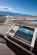 "Tourists walking on the boardwalk at Badwater with a ""Birth of Death Valley"" sign - Death Valley National Park, California"