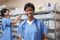Portrait of female doctor, nurse standing by shelves with medical supplies in background
