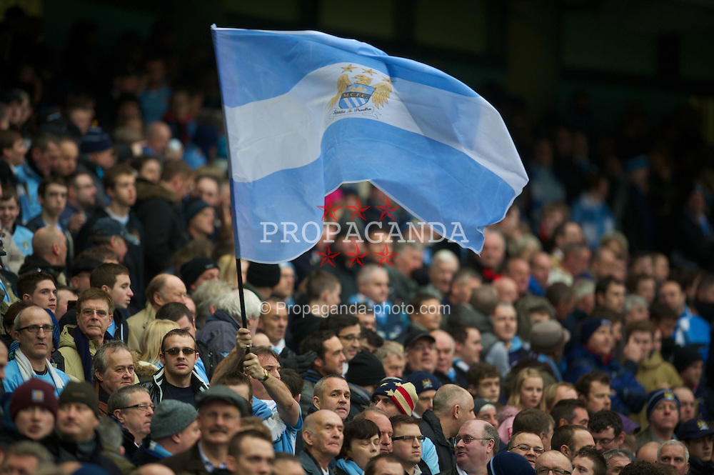 MANCHESTER, ENGLAND - Sunday, January 8, 2012: A Manchester City supporter waves a flag during the FA Cup 3rd Round match against Manchester City at the City of Manchester Stadium. (Pic by David Rawcliffe/Propaganda)