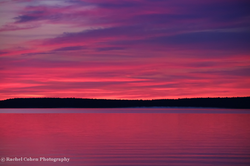 &quot;Dawn's Early Light&quot;<br /> <br /> Beautiful pink and purple hues and Mackinac Island in silhouette in a lovely sunrise image over Lake Huron in Michigan's Upper Peninsula!<br /> <br /> Sunrise Images by Rachel Cohen