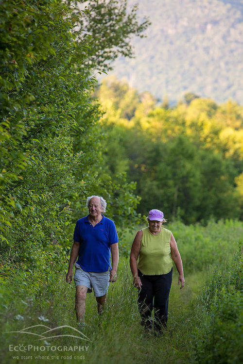 A couple walks on the edge of a forest in Duxbury, Vermont.