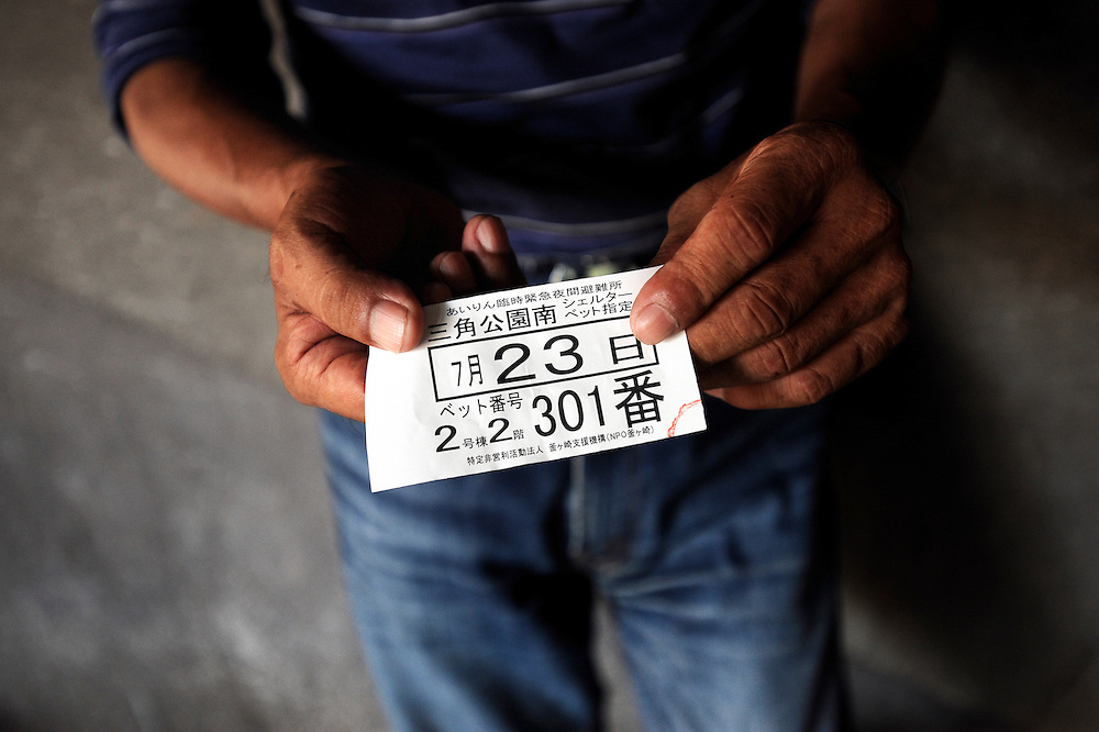 """""""Koji"""" Yamaguchi, a day laborer who has no fixed abode of residence, shows the ticket he received indicating his bed number at a shelter in the Kamagasaki district of Osaka, Japan."""