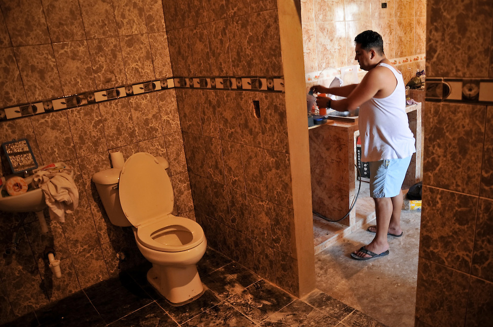 "Tairon Jaimes, 35, has one of the nicest home in the ""Tower of David."" Jaimes moved to the skyscraper after his home was destroyed by a mudslide four months ago. A carpenter by trade, Mr. Jaimes has installed tile and even crown molding that he made by hand."
