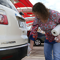 Tiffany Warren wipes down her vehicle Saturday after getting it washed at Shine Time Superwash at Crosstown