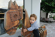 young child of two plays on a wooden horse Photographed in Austria