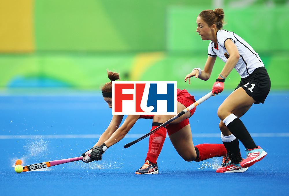 RIO DE JANEIRO, BRAZIL - AUGUST 10:  Lisa Schutze of Germany and Kiju Park of Korea battle for the ball during the Women's Pool B Match between Germany and Korea on Day 5 of the Rio 2016 Olympic Games at the Olympic Hockey Centre on August 10, 2016 in Rio de Janeiro, Brazil.  (Photo by Mark Kolbe/Getty Images)
