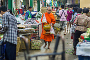 09 OCTOBER 2012 - BANGKOK, THAILAND:  A Buddhist monk walks through the Bangkok Flower Market. Most males in Thailand enter the Sangha (become Buddhist monks) at least once in their lives. Their time in the Sangha may be as short as a few weeks or as long as a lifetime commitment. The Bangkok Flower Market (Pak Klong Talad) is the biggest wholesale and retail fresh flower market in Bangkok. It is also one of the largest fresh fruit and produce markets in the city. The market is located in the old part of the city, south of Wat Po (Temple of the Reclining Buddha) and the Grand Palace.    PHOTO BY JACK KURTZ