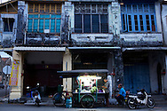 A hawker stall in front of a row of crumbling shop houses in GT.