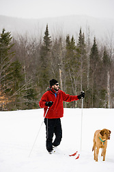 A man cross country skiing with his dog on the Catamount Trail in Stowe, Vermont. Model Release.