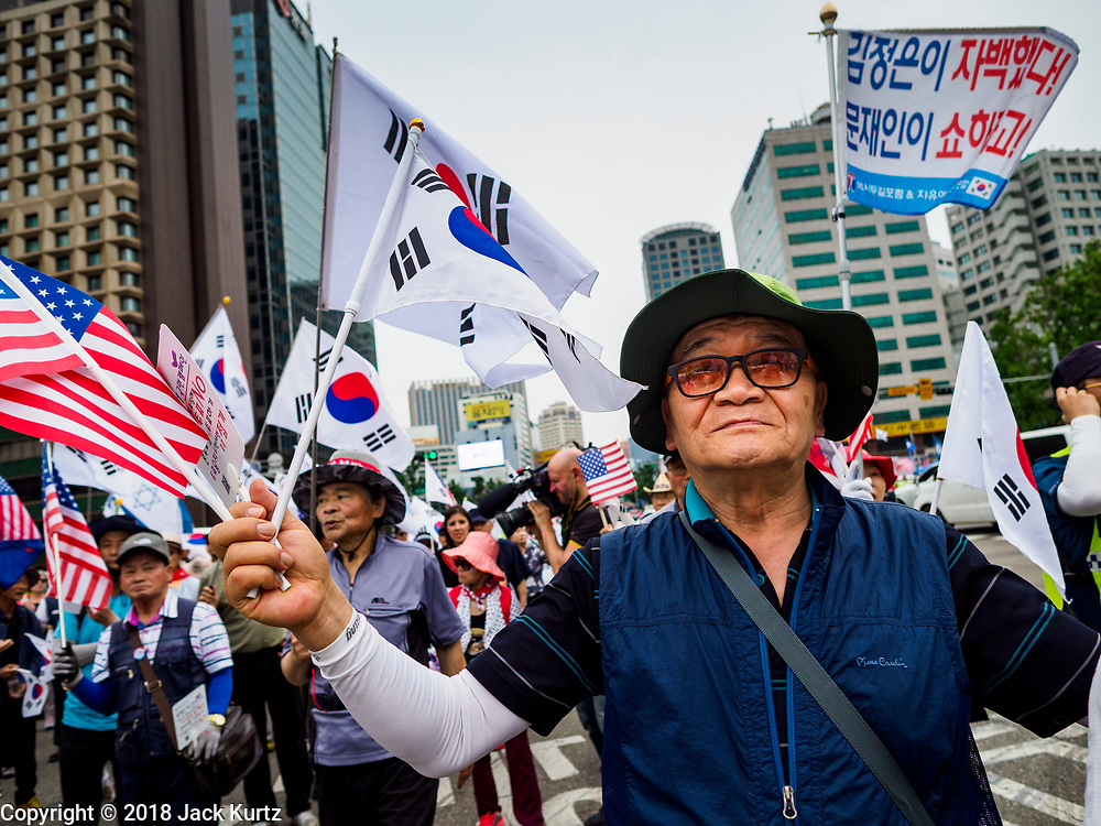 09 JUNE 2018 - SEOUL, SOUTH KOREA: A man with South Korean and American flags marches in a pro-American rally in downtown Seoul. Participants said they wanted to thank the US for supporting South Korea and they hope the US will continue to support South Korea. Many were also opposed to ongoing negotiations with North Korea because they don't think Kim Jong-un can be trusted to denuclearize or to not attack South Korea.    PHOTO BY JACK KURTZ