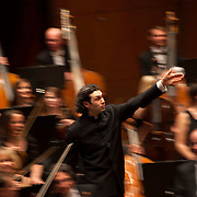 "March 11, 2013 - New York, NY : .Conductor Vladimir Jurowski, center, gestures toward the London Philharmonic Orchestra, as he acknowledges the audience's applause after a performance of Gustav Mahler's Symphony No. 5 in C-sharp minor (1901-02), part of Lincoln Center's ""Great Performers"" series at Avery Fisher Hall on Monday evening..CREDIT: Karsten Moran for The New York Times *The blurred/motion effect is created by using a slow shutter speed and panning the camera with the conductor.* **This image is a crop variation.**"