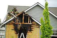 Coeur d'Alene firefighters saw through the eave of a roof in the Sunshine Meadows subdivision after a fire destroyed two rooms in a home Wednesday in north Coeur d'Alene. A 12-year-old boy who was home sick from school evacuated his two dogs, exited the house and called 911 when alerted to the fire.
