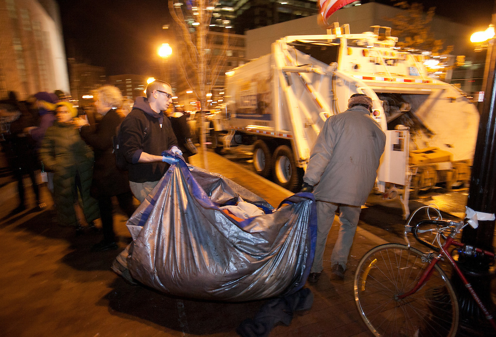Boston, MA 12/08/2011.Occupy Boston members carry a tarp loaded with trash to a waiting garbage truck as the city of Boston's deadline to vacate Dewey Square draws near on Thursday evening..Alex Jones / www.alexjonesphoto.com