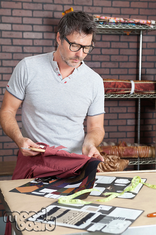 Mature male fashion designer matching color of shirt with cloth swatch