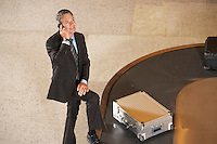 Business man using mobile phone at luggage carousel in airport