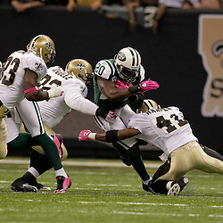 2009 October 04: New Orleans Saints defenders Darren Sharper (42) and Remi Ayodele (92) and Bobby McCray (93) close in on New York Jets running back Thomas Jones (20) during a 24-10 win by the New Orleans Saints over the New York Jets at the Louisiana Superdome in New Orleans, Louisiana.