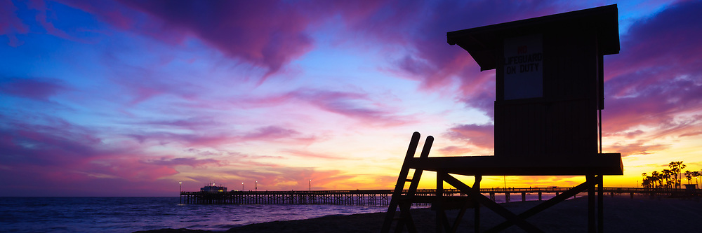 Sunset panorama photo of Lifeguard Tower B and Balboa Pier in Newport Beach California. The sky had beautiful dramatic clouds with a mix of blue, purple, and orange colors. Newport Beach is a popular coastal beach city along the Pacific Ocean in Orange County Southern California. Panoramic photo ratio is 1:3. Copyright ⓒ 2017 Paul Velgos with All Rights Reserved.