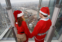 © licensed to London News Pictures. London, UK 15/12/2013. People dressed as Father Christmas experiencing The View from The Shard for free as the Shard offers complimentary access to the guests dressed in a full traditional Santa outfit to celebrate the skyscraper's first Christmas on Sunday, 15 December 2013. Photo credit: Tolga Akmen/LNP