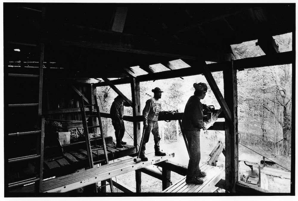 Barnwrights Scott Hatch, right, Dave Rose, center, and Joe Marshall, left, at work on a barn in Hollis, ME. They are placing a new crossbeam to shore up the structure of the barn.