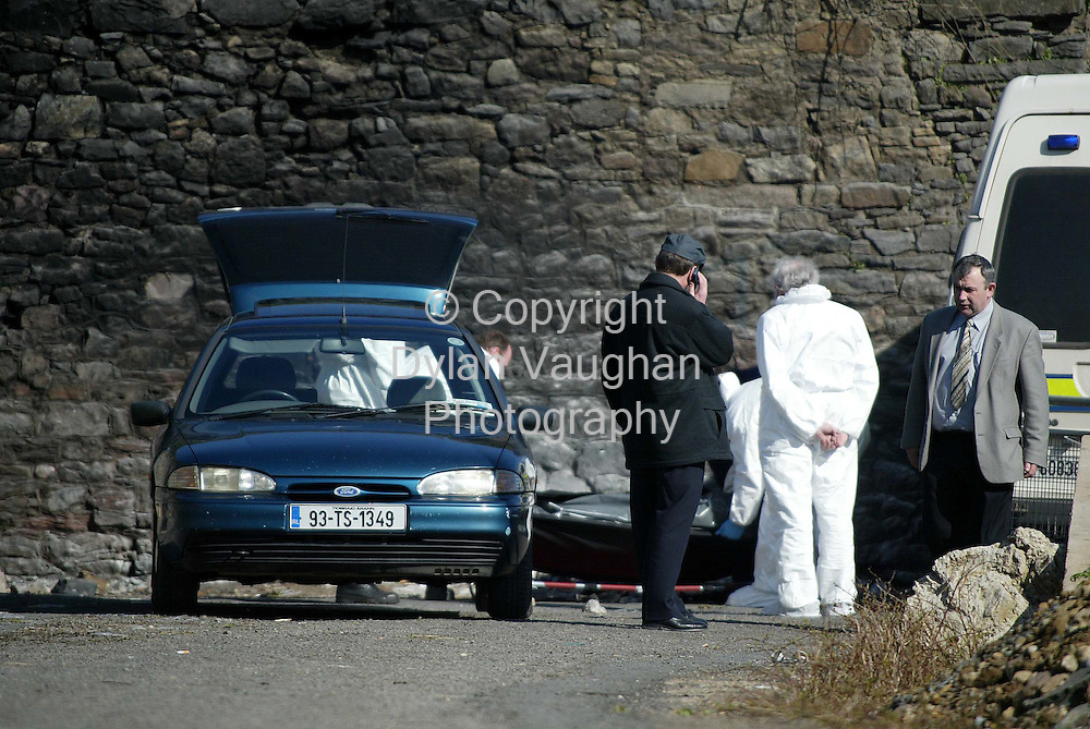 13/3/2002 Irish Independent News.Gardai pictured lifting the body of Francis McDonagh into a car in Carrick-On-Suir Co Tipperary yesterday..Picture Dylan Vaughan