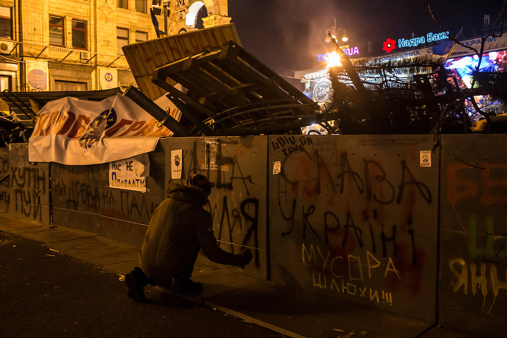 KIEV, UKRAINE - DECEMBER 3: A protester paints graffiti on a barricade during a rally in Independence Square on December 3, 2013 in Kiev, Ukraine. Thousands of people have been protesting against the government since a decision by Ukrainian president Viktor Yanukovych to suspend a trade and partnership agreement with the European Union in favor of incentives from Russia. (Photo by Brendan Hoffman/Getty Images) *** Local Caption ***