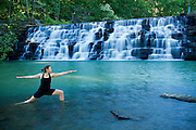 Woman practices yoga in Warrior pose by a waterfall.